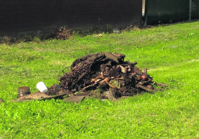 Op een groenstrook tussen de huizen ligt een stinkende berg afval te rotten in de zon. Foto Coen Hagenaars