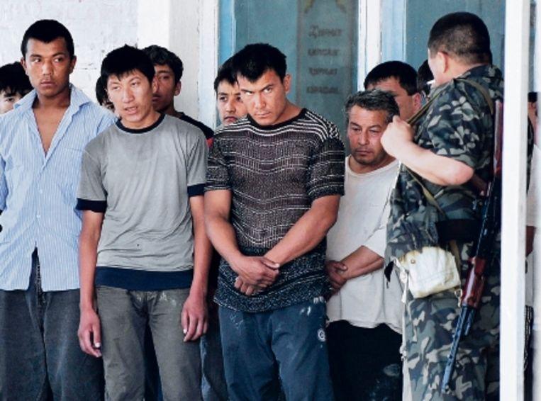 Kirgizische politiemannen fouilleren etnische Oezbeken in een dorp vlakbij Osj. (FOTO AFP) Beeld