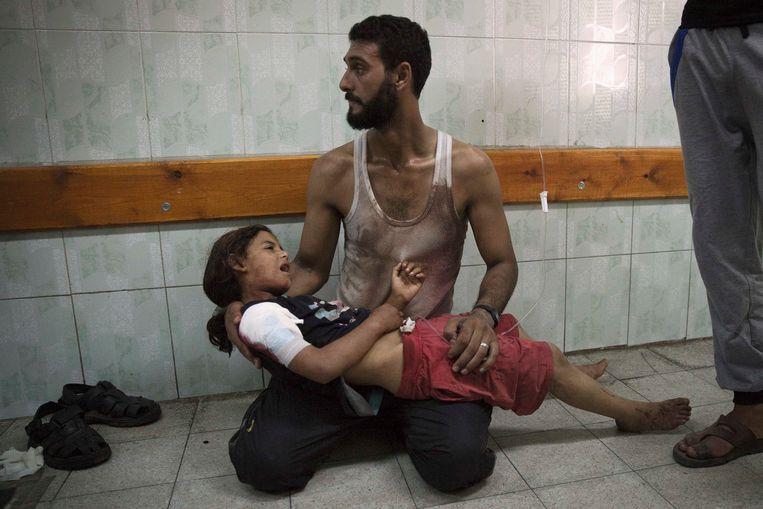 Een Palestijnse man houdt een gewond meisje vast bij een ziekenhuis in de Gazastrook. Beeld REUTERS