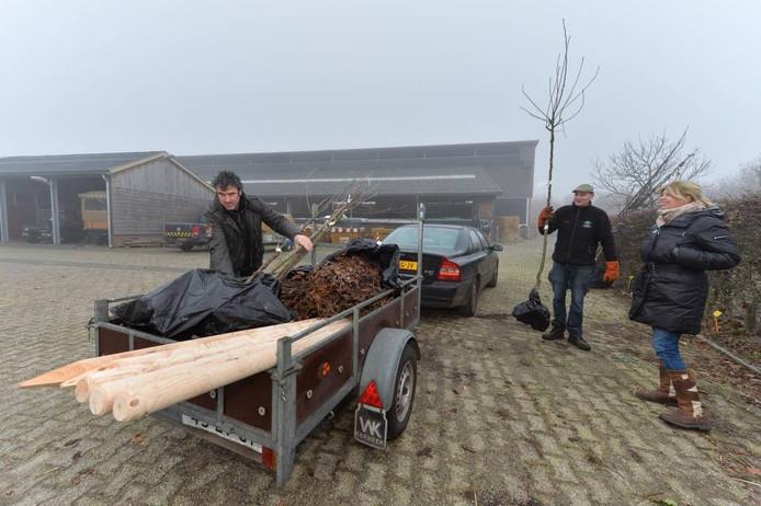 Bert (links) en Liesbeth Hoenink komen bomen, stuiken en palen ophalen. Adviseur Eward Timmersman (midden) van landschapbeheer Gelderland kijkt toe.