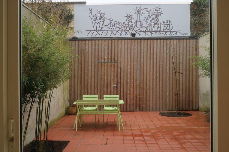 De achterwand van de tuin verandert regelmatig, elke nieuwe artiest mag er zijn ding mee doen.