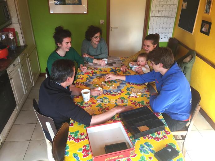 Een deel van het gezin, Filip, Loes, Nancy, Janneke, Miel en Jef, speelt samen een spel aan tafel.