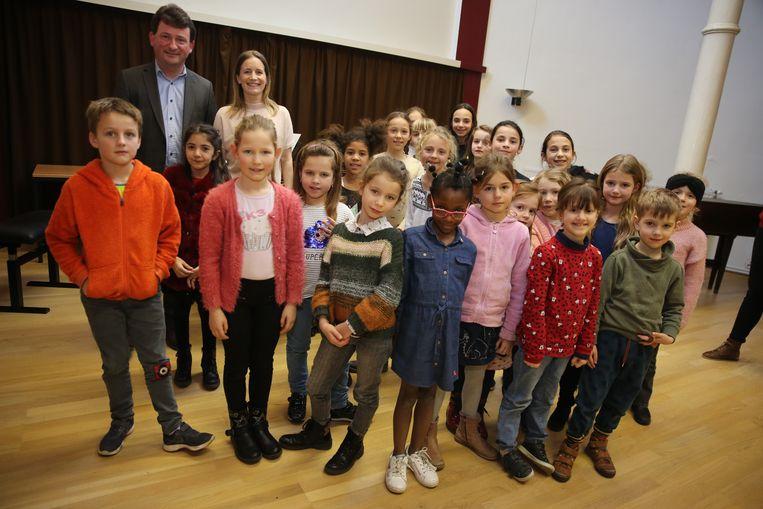 Directeur Stijn Hanssens en schepen van Onderwijs Dieuwertje Poté (CD&V) met de kinderen van het  kinderkoor van de Servaisacademie die volgend jaar dus ook op de Kunstacademie Halle zitten.