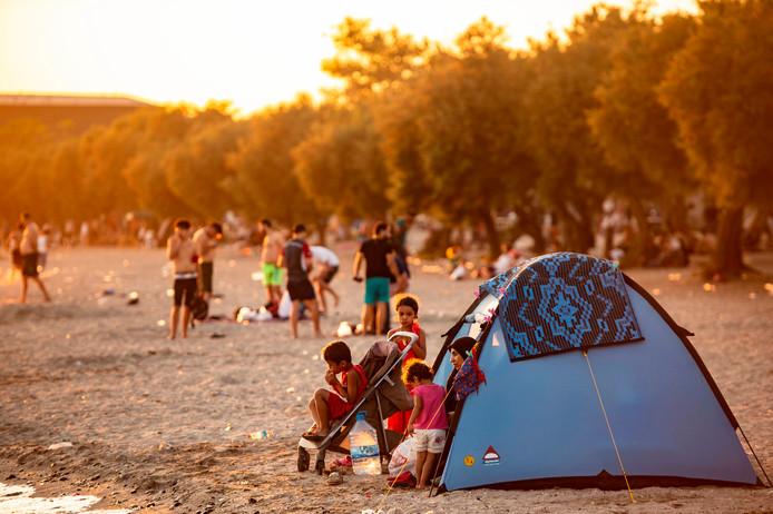 Een Syrische familie bivakkeert in een tent op het strand van Menekse bij Istanboel.