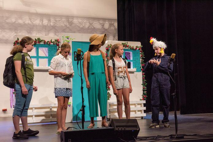 Leerlingen van De Triolier repeteren voor de schoolmusical. Dat doen ze vanwege de coronamaatregelen in de grote zaal van gemeenschapshuis De Borgh.