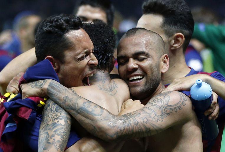 Dani Alves (rechts) viert het winnen van de Champions League.