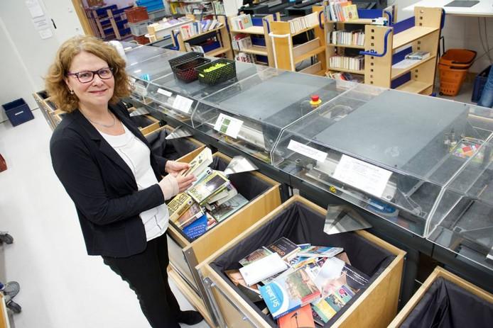 Ria Oudega bij de machine die terugbezorgde boeken klassificeert. Foto: Marc Pluim