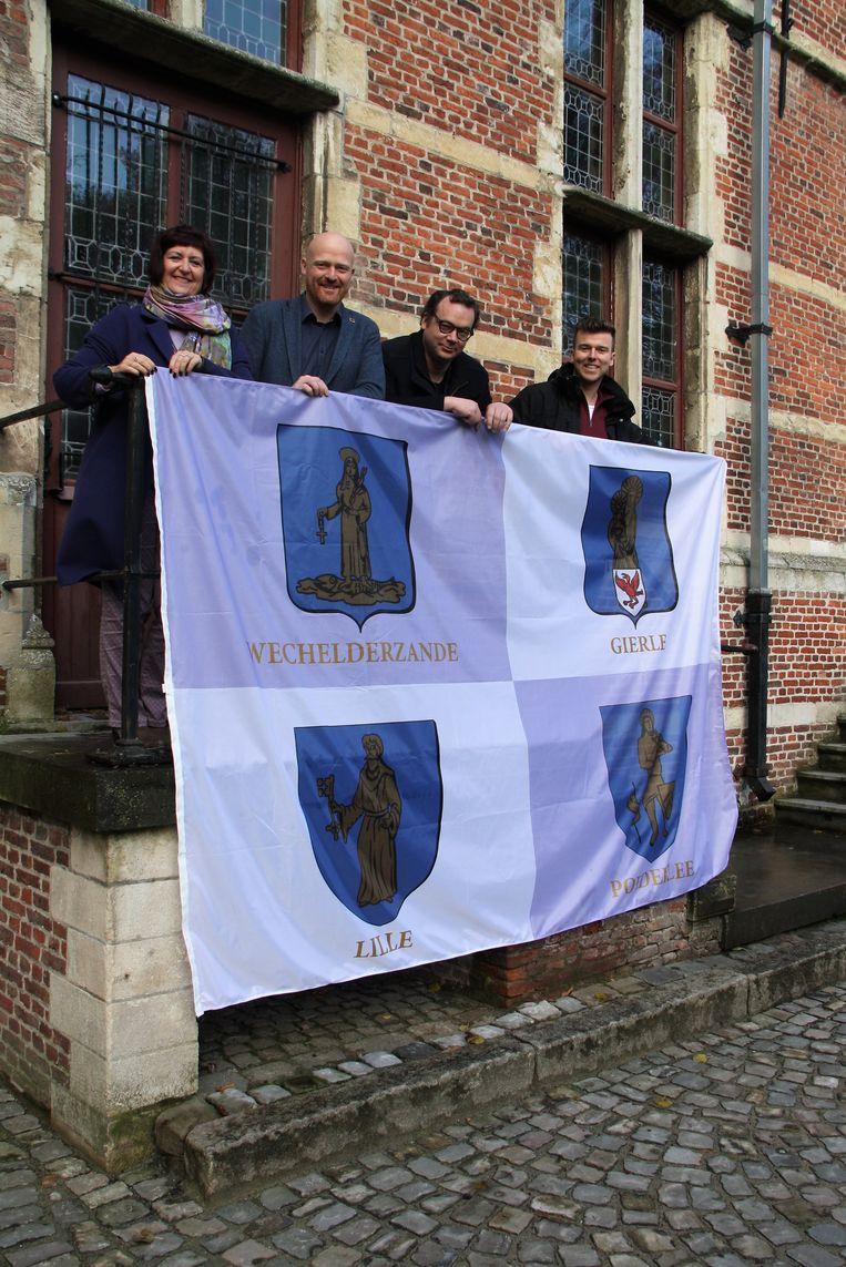 Burgemeester Marleen Peeters en schepenen Luc De Backer, Tom Kersemans en Chiel Danckers poseren met de verzamelvlag met de vier wapenschilden. Aan de oude gemeentehuizen wapperen vlaggen met de individuele wapenschilden.