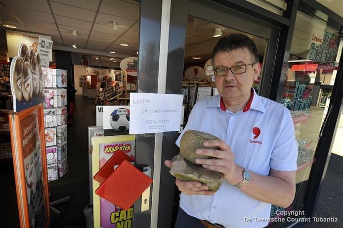Eigenaar Gerrit Brinkman, met in zijn handen de stenen die door dieven gebruikt zijn.