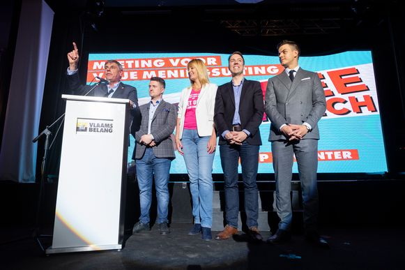 De Britse anti-islamactivist Tommy Robinson (tweede van links) en Dries Van Langenhove (rechts) luisteren naar Filip Dewinter.