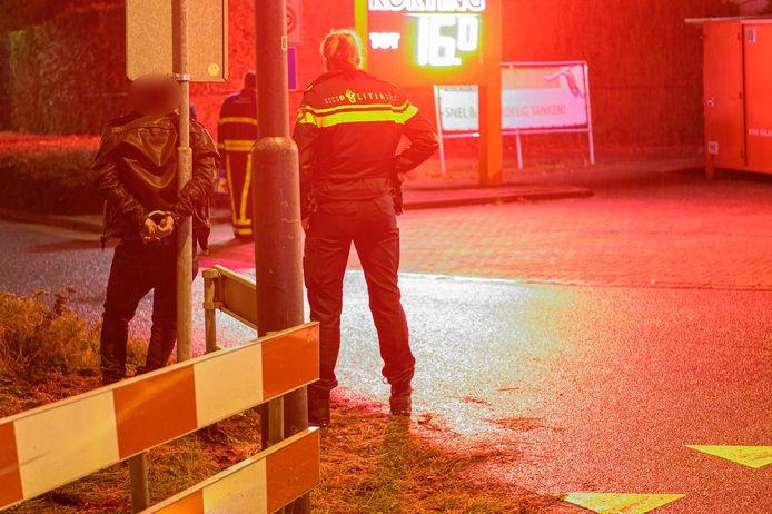 Zes mannen zijn in de buurt van de loods aangehouden. Een man werd met handboeien vastgebonden aan de paal van een verkeersbord. Een ander werd door agenten naar de grond gewerkt.