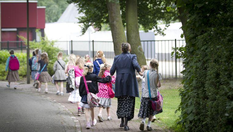 Moeders brengen kinderen naar de reformatorische basisschool Eben-Haezer in Barneveld, waar in een kleuterklas vermoedelijk kinderen met mazelen waren besmet. (Archieffoto juni 2013) Beeld null