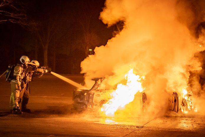 Brandweerlieden blussen een brandende auto op de parkeerplaats aan de Oud Wulfseweg in Houten.