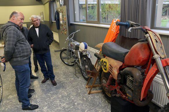 Enkele bezoekers inspecteren een oude motor.