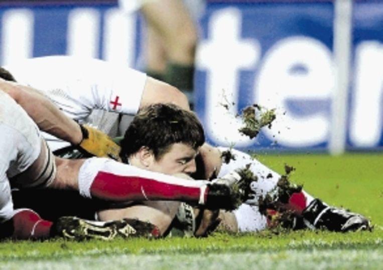 De Ier OÂ¿Driscoll verdwijnt bijna onder het gras, maar scoort wel een try in de wedstrijd tegen Engeland. Ierland won met 14-13. ( FOTO REUTERS) Beeld REUTERS