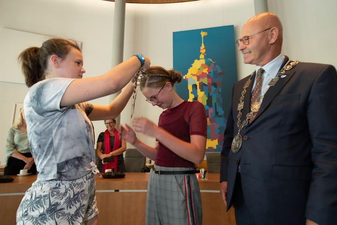 Vorig jaar kreeg Rosalijn van Zijtveld de ambtsketting van de toenmalige jeugdburgemeester, Fiene d' Alfonso (l). Rosalijn draagt geeft morgen het stokje over aan Franco Koelewijn.