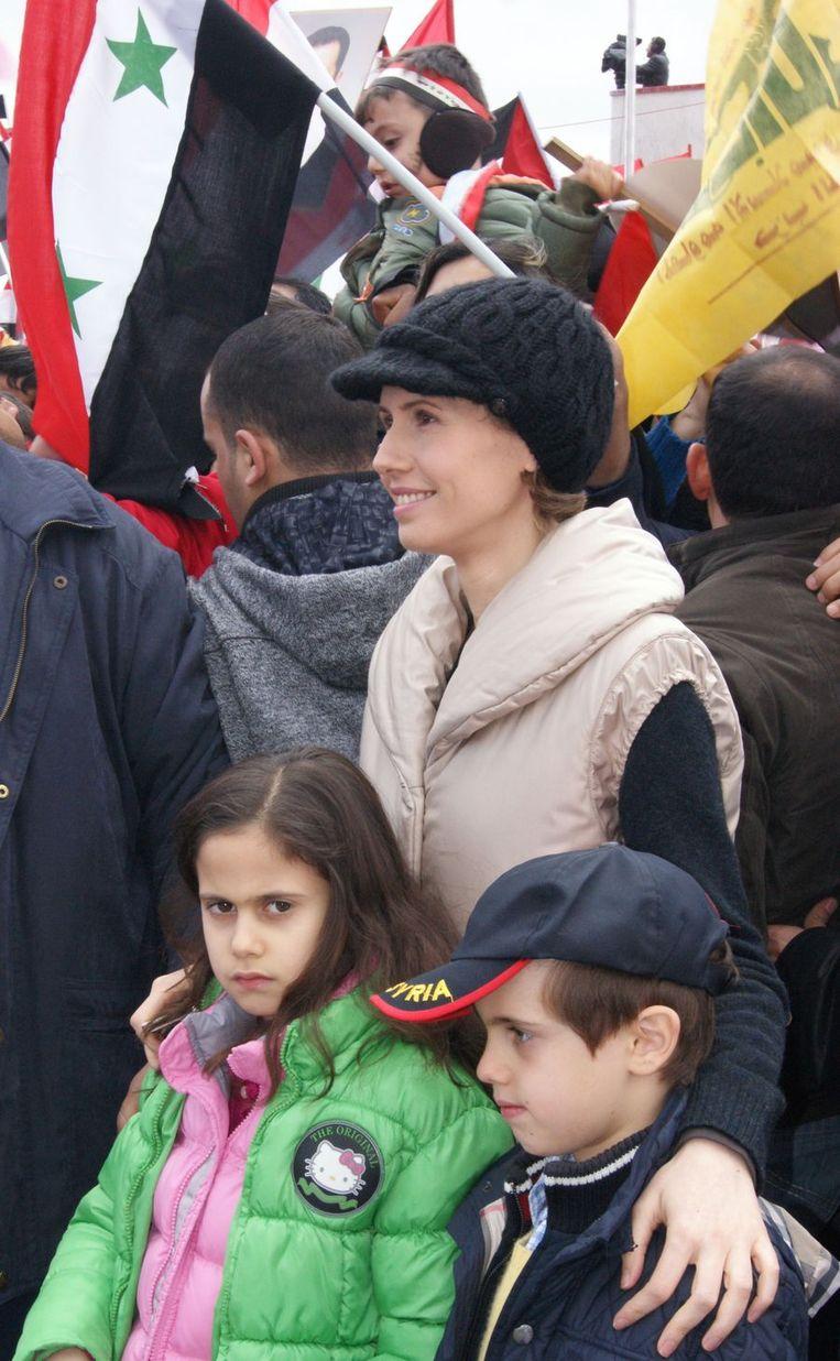 De vrouw van president Assad luistert met haar kinderen naar een toespraak van haar man op een demonstratie van zijn voorstanders. Beeld afp