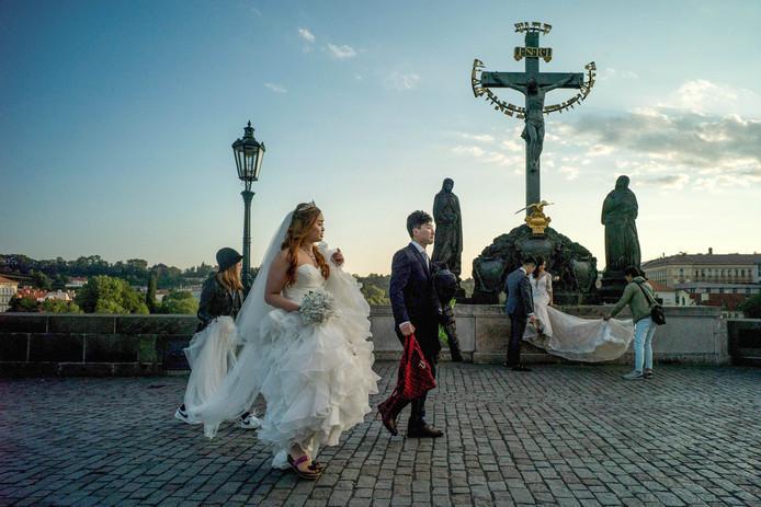Twee Zuid-Koreaanse bruidsparen laten zich fotograferen op de Karelsbrug in Praag. Foto Michal Cizek