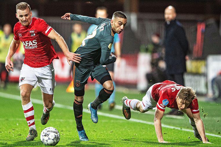 Hakim Ziyech wil met de bal dribbelen maar twee AZ-spelers voorkomen dat. Beeld null