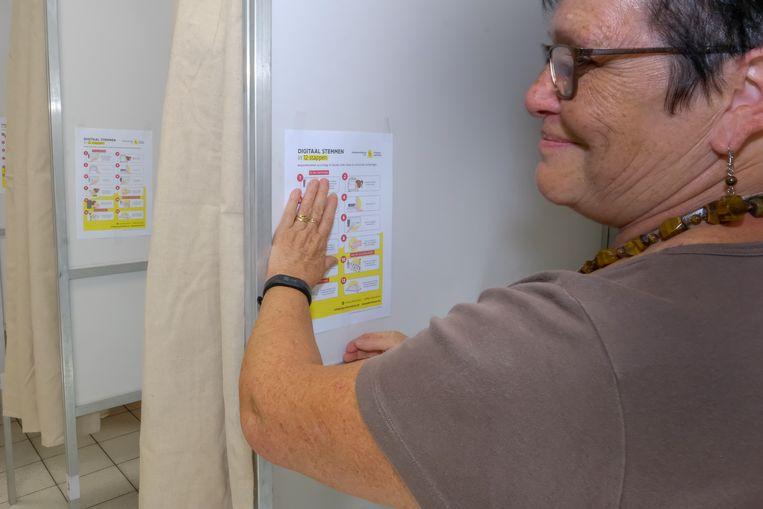 Verantwoordelijke van het kiesbureau hangt de nodige info voor de kiezers.