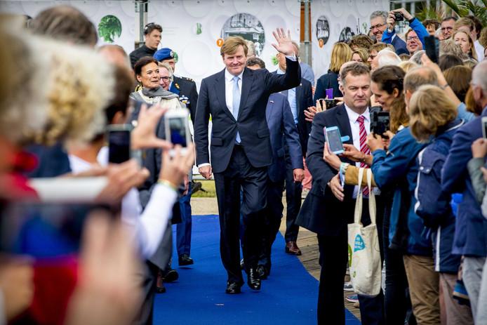 Koning Willem-Alexander zwaait naar zijn fans tijdens de viering van 100 jaar Wageningen Universiteit.