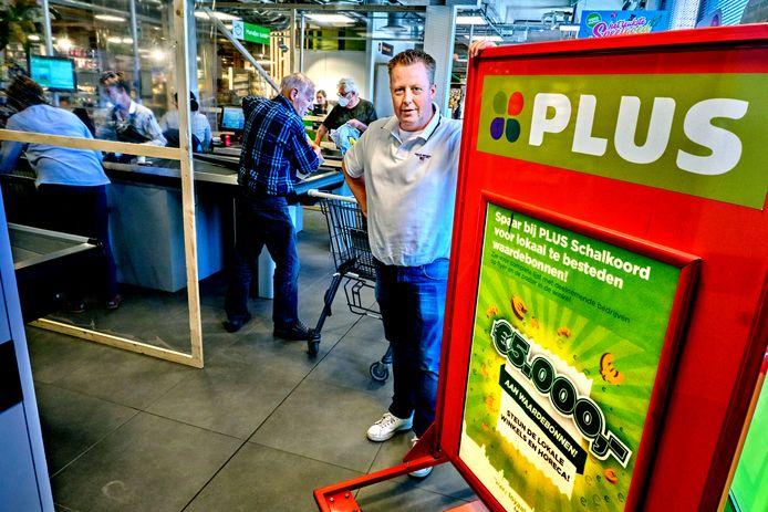 Mario van der Linden van PLUS Schalkoord attendeert op het enorme bord om lokale ondernemers in NIeuw-Beijerland te steunen.