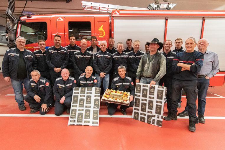 Het brandweerkorps met bakker Luc met de hoed. Klaar om te beginnen te smullen