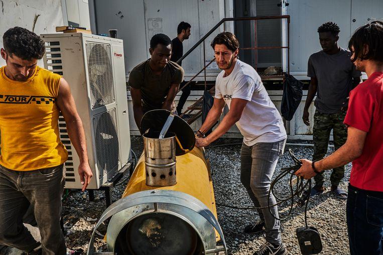 Adil Izemrane (wit shirt) verplaatst samen met inwoners van de Olive Grove een heteluchtkanon bedoeld om tenten te verwarmen in de winter. Beeld Joris van Gennip