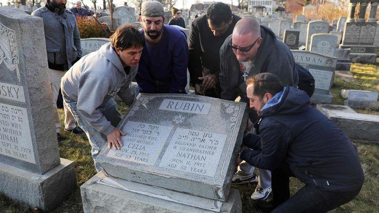 Mannen helpen een grafsteen overeind te zetten op de Joodse Mount Carmel Cemetery. Beeld afp