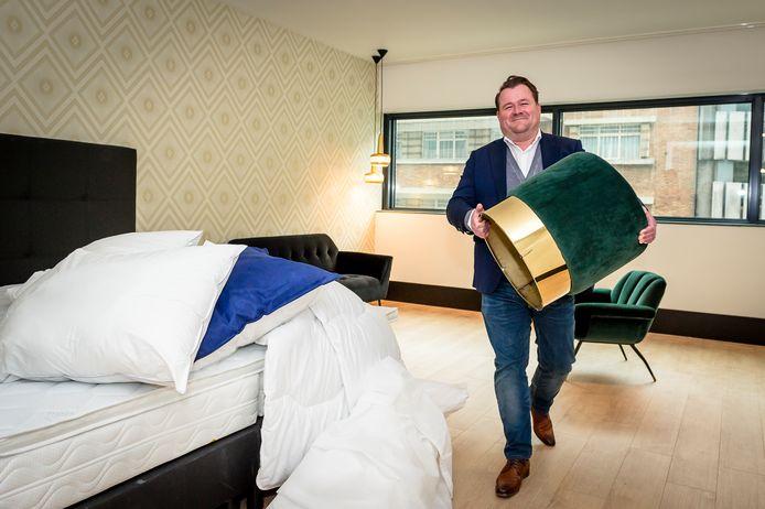 Michiel Brandhorst sjouwt met een poef in een kamer van The James.