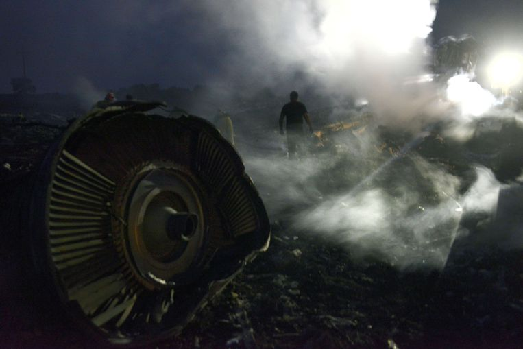 Een man temidden van de wrakstukken van vlucht MH17.  Beeld AFP