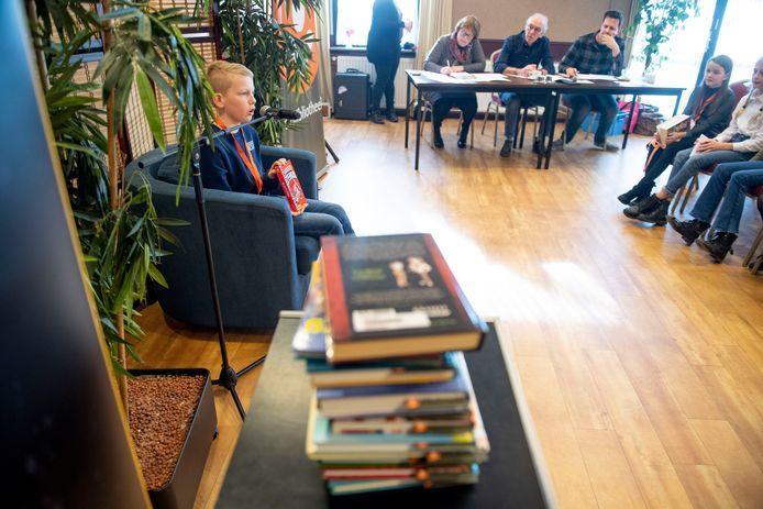 Onder toeziend oog van de juryleden Henriëtte Gerrits, Theo de Putter en Jeroen de Kleine boeit Thomas Pots het publiek met zijn voordracht.