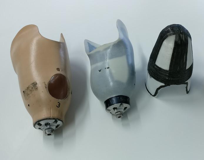 Verschillende versies van de koker van een onderbeenprothese. Links en midden een huidig model, rechts een prototype van thermoplastisch composiet.