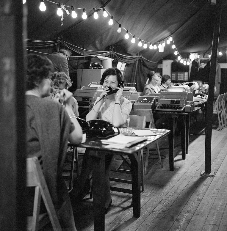 Telefonistes in een tot perscentrum opgetuigde tent, bijgelicht door feestverlichting. Beeld Hollandse Hoogte