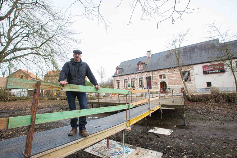 Wim Demunter, de vriend van restaurantuitbaatster Barbara Beeckman, op het brugje dat hij op een dag tijd bouwde.