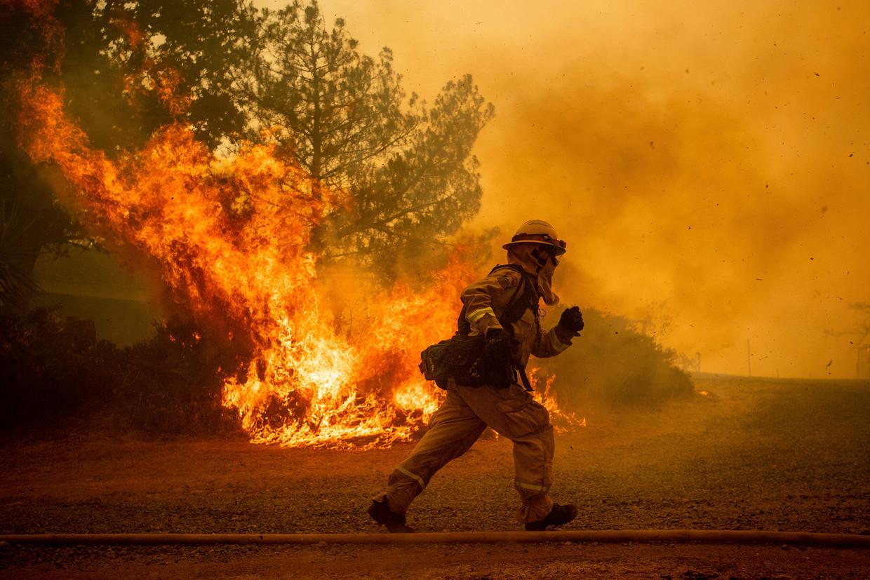 Een brandweerman in Californië haast zich om een huis te beschermen tegen de natuurbrand. De woning gaat uiteindelijk toch in vlammen op.