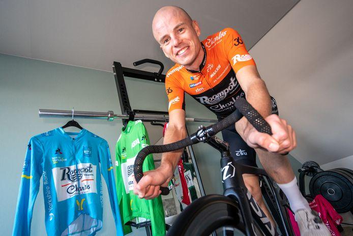 Jesper Asselman, wielrenner, hier aan het trainen op zijn zolderkamer. Op de achtergrond zijn grootste 'trofee', de leiderstrui in 'Tour de Yorkshire 2019'.