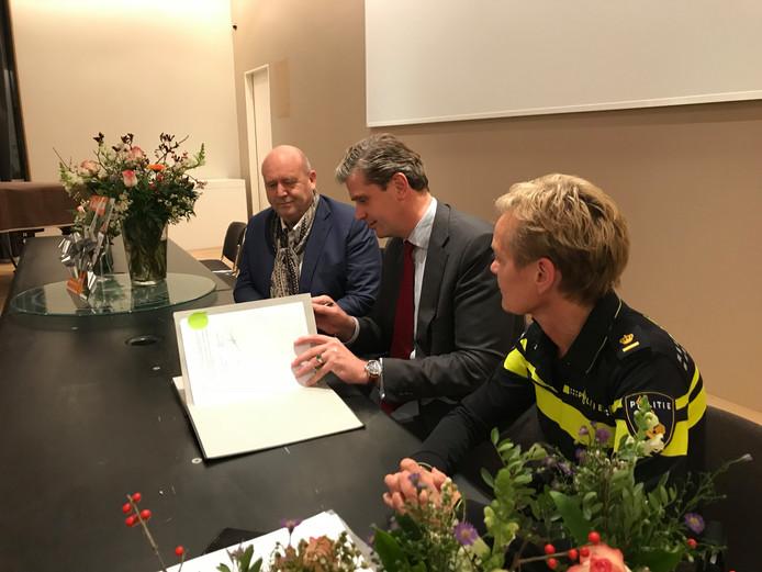 Burgemeester Wouter Kolff (midden) ondertekent het convenant samen met de politie en horeca-ondernemers, waaronder Ad Janssen.