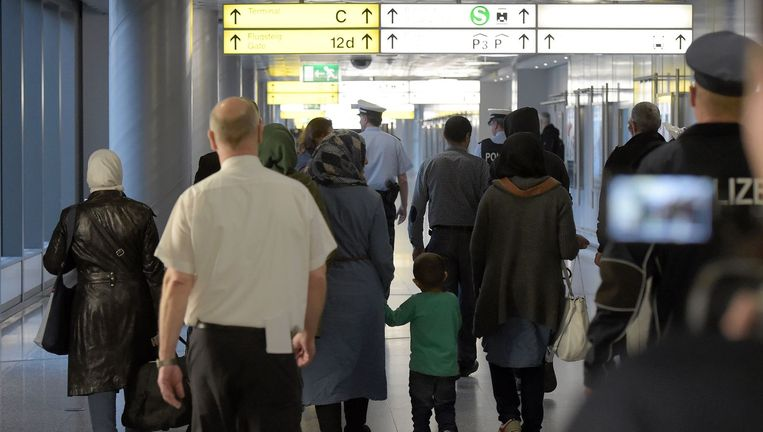 Politiemannen escorteren een groep vluchtelingen op de luchthaven van Hannover. Beeld afp