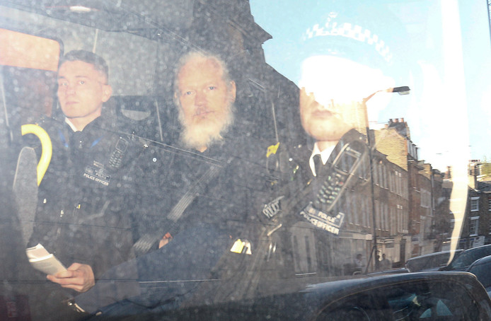 Julian Assange verlaat onder politiebegeleiding de rechtbank in Londen.