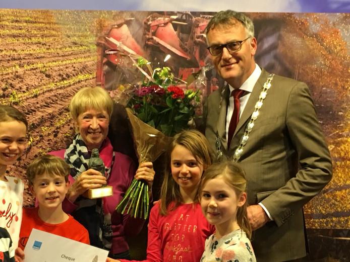 Hetty Boon-Bierhoff, omringd door haar kleinkinderen, kreeg de Moergestelse vrijwilligersprijs uit handen van burgemeester Hans Janssen
