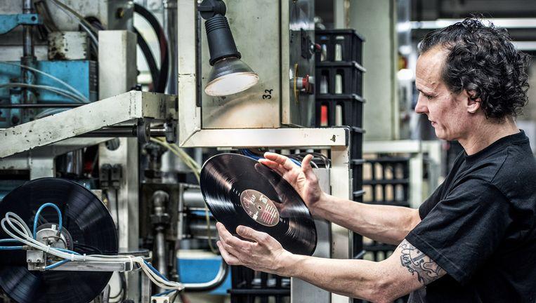 Na het persen gaan de platen in de hoes. Een medewerker controleert een exemplaar. Beeld Raymond Rutting