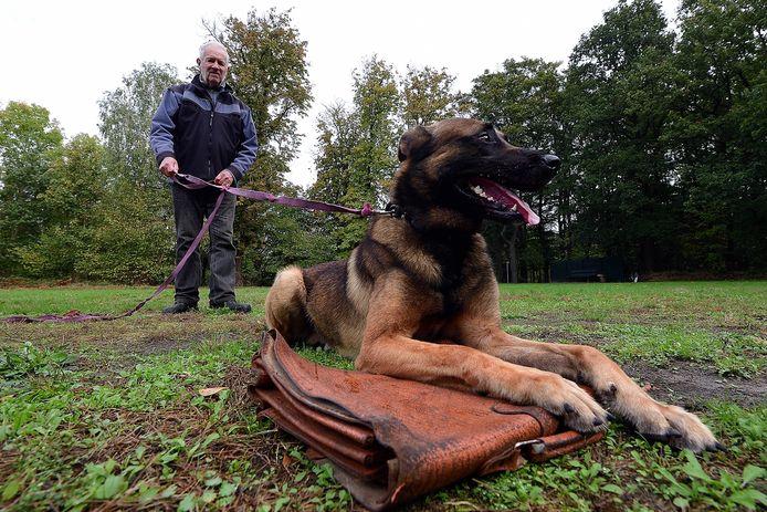 De hond die de opdracht kreeg de tas te bewaken, geeft geen krimp. De hand kreeg geen kan om in de buurt te komen.