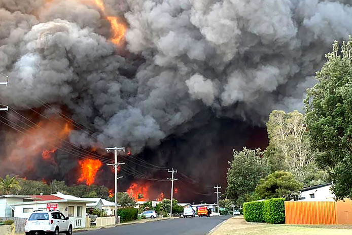 Een vlammenzee en grote rookwolken van een bosbrand in Harrington in de Australische deelstaat New South Wales.