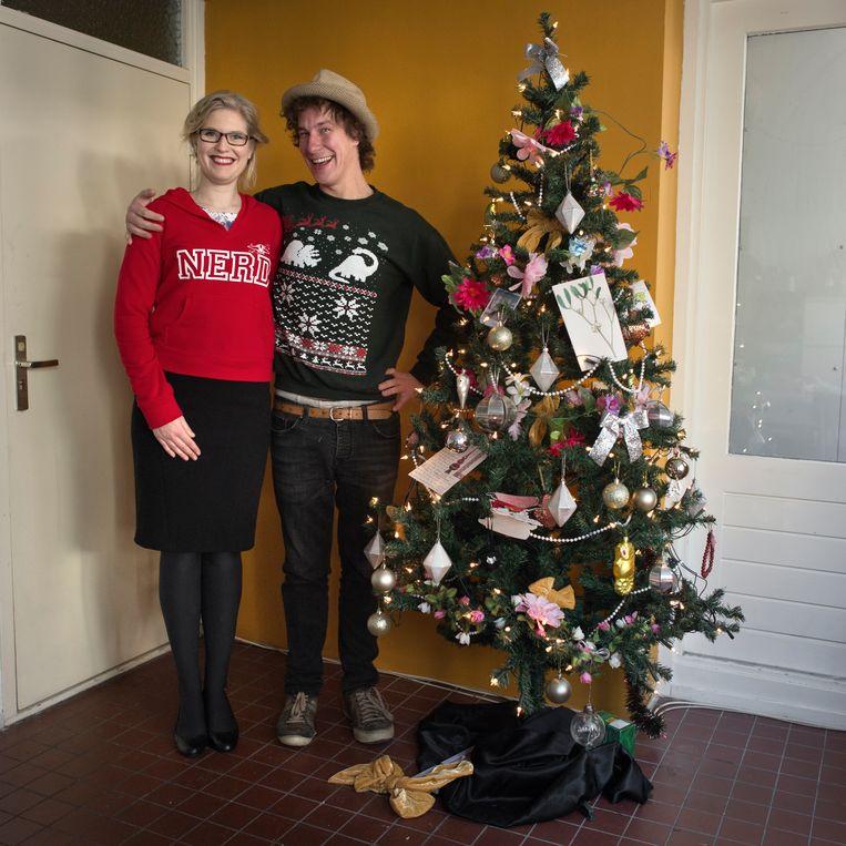 Juliëtte Verberk en haar huisgenoot Dolf Huybers eind januari bij de kunstkerstboom die ze met alle versieringen erbij voor 20 euro hebben gekocht, in de uitverkoop uiteraard. Beeld Joost van den Broek