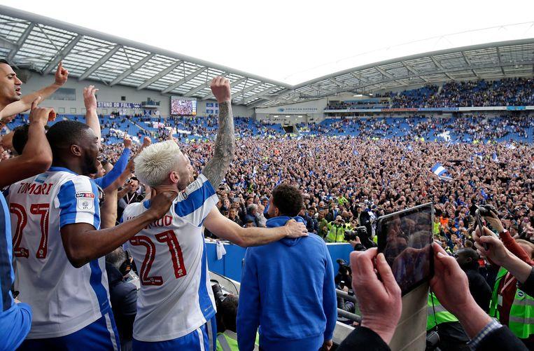 Brighton-spelers met hun fans vieren feest in het stadion van de club. Beeld Photo News