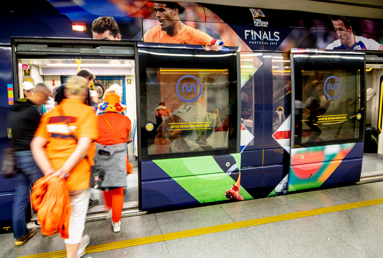 Nederlandse fans betreden in Porto de metro waarop de afbeelding van Virgil van Dijk te zien is.