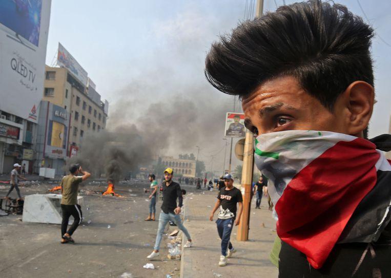 Een demonstrant heeft een Iraakse vlag over zijn gezicht geknoopt.  Beeld null