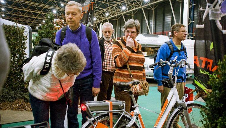 Bezoekers van de vakantiebeurs bekijken een elektrische fiets. Accu's zijn na 3 tot 5 jaar aan vervanging toe, al kunnen ze volgens de ANWB bij goede behandeling 7 jaar mee. Beeld Roel Burgler / Hollands Hoogte