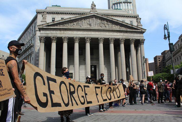 Demonstranten met een spandoek met daarop de naam van George Floyd voor de rechtbank van New York. Beeld Karlijn van Houwelingen